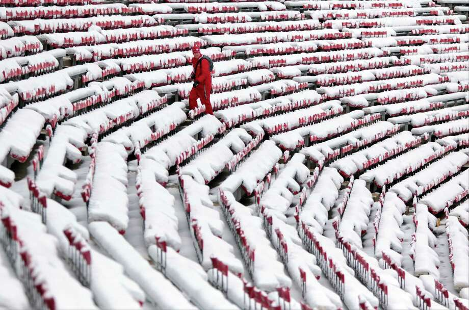 Daron Jones, University of Wisconsin's associate director of events and operations, trudges through the snow-covered west stands before an NCAA college football game between Wisconsin and Northwestern at Camp Randall Stadium in Madison, Wis., Saturday, Nov. 21, 2015. The first significant snowstorm of the season blanketed some parts of the Midwest with more than a foot of snow and more was on the way Saturday, creating hazardous travel conditions and flight delays. (Michael P. King/Wisconsin State Journal via AP) Photo: Michael P. King, Associated Press / Wisconsin State Journal