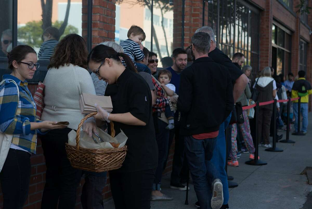 Yier Moua hands out doughnut holes at the line forming at the SFMade holiday gift fair held at the Pintrest building on Saturday, Nov. 21, 2015 in San Francisco, Calif.
