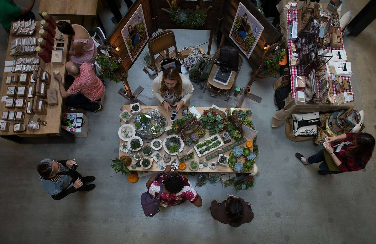 Gift shoppers look at the wares sold by local businesses at the SFMade holiday gift fair held at the Pintrest building on Saturday, Nov. 21, 2015 in San Francisco, Calif.