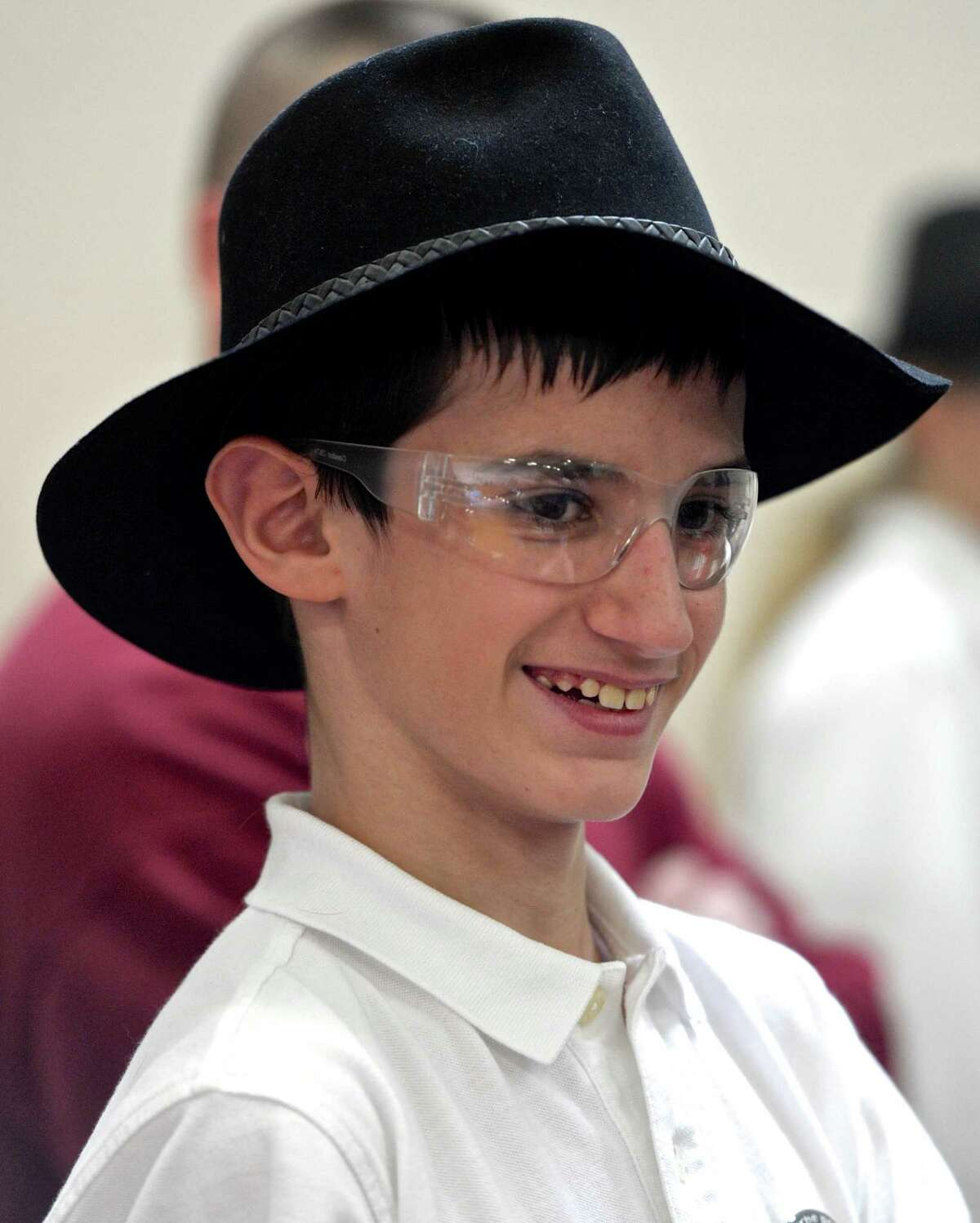"""Tyler Anvryzeck, 12, from the """"Northwest Regional Gearheads"""" team, displays his hat that the team was wearing while they compete in the Connecticut FIRST Tech Challenge (FTC) robotics qualifying event, held at Ridgefield Academy. Saturday, November 21, 2015, in Ridgefield, Conn."""