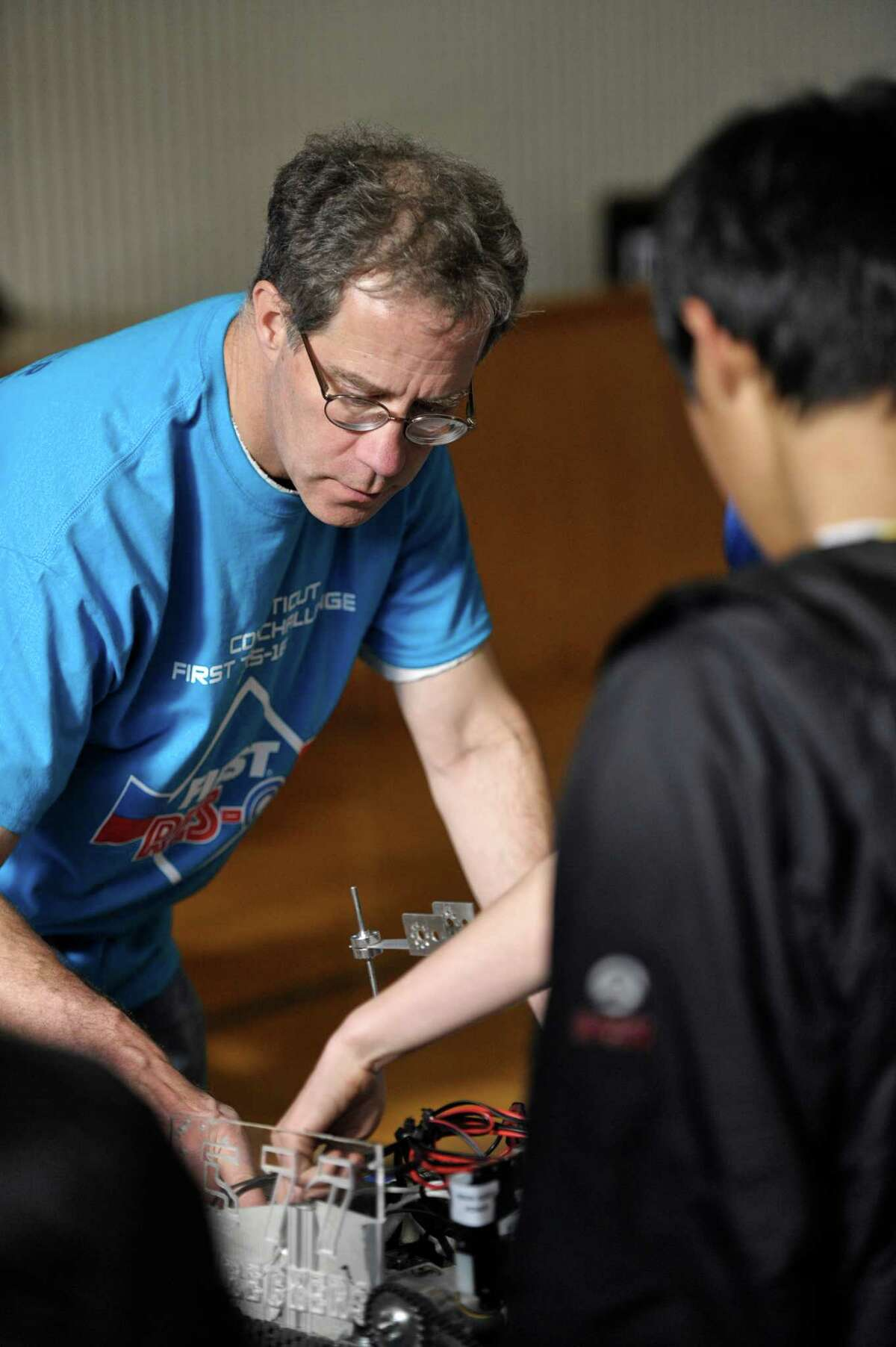 George Riehm, of New Fairfield, inspects a robot before the Connecticut FIRST Tech Challenge (FTC) robotics qualifying event, held at Ridgefield Academy. Riehm is a mentor for a team from Danbury but also volunteers with the competition. Saturday, November 21, 2015, in Ridgefield, Conn.