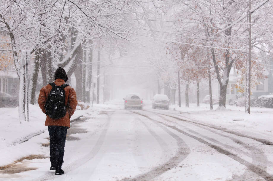 A man walks down a snowy street  in Jackson, Mich. Saturday, Nov. 21, 2015.  The first significant snowstorm of the season blanketed some parts of the Midwest with more than a foot of snow and more was on the way Saturday, creating hazardous travel conditions and flight delays. (Jessica Christian/Jackson Citizen Patriot via AP) LOCAL STATIONS OUT; LOCAL INTERNET OUT; MANDATORY CREDIT Photo: Jessica Christian, MBI / Jackson Citizen Patriot