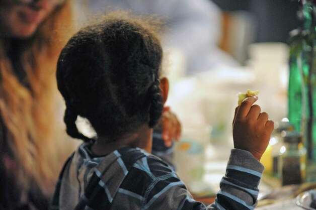 A young boy enjoys a full Thanksgiving style dinner during the South End Children's Cafe at the Reigning Life Family Church on Thursday Nov. 19, 2015 in Albany, N.Y. (Michael P. Farrell/Times Union) Photo: Michael P. Farrell / 10034320A