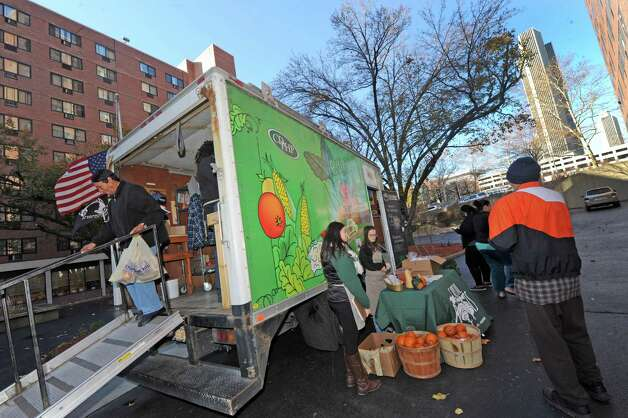 The Veggie Mobile, a project of Capital Roots/Capital District Community Gardens, that provides low-priced fresh fruits and vegetables to underserved inner-city areas makes a stop at the South Mall Towers on Friday Nov. 20, 2015 in Albany, N.Y. (Michael P. Farrell/Times Union) Photo: Michael P. Farrell / 10034322A