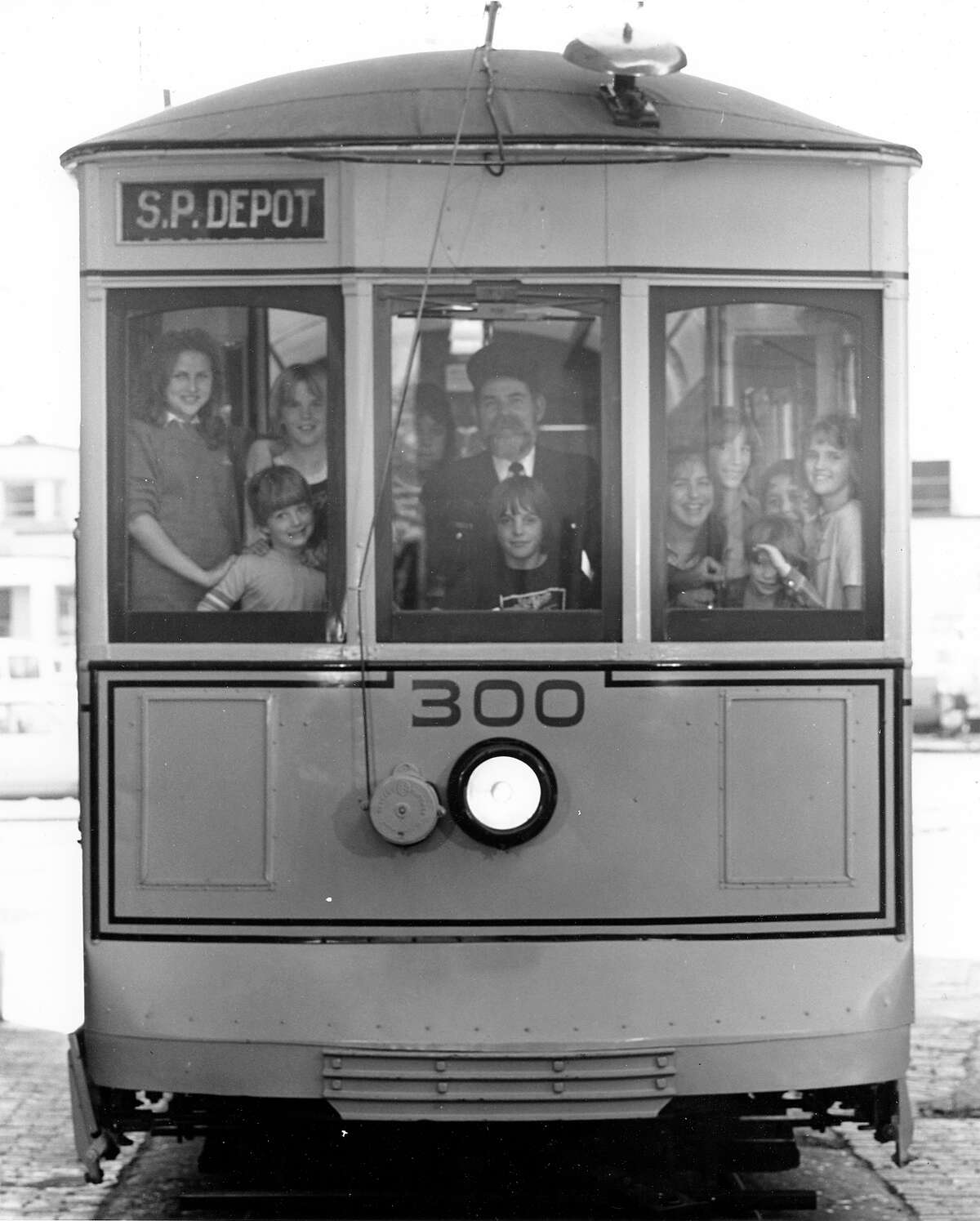 """Engineer, Leonard """"Smitty"""" Schmidt, gives children a ride on the newly restored """"Old 300"""" streetcar, October 9, 1982."""