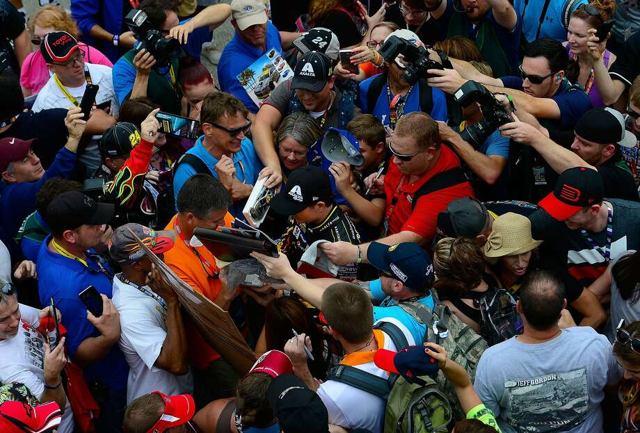 Fans surround Jeff Gordon after practice for the NASCAR Sprint Cup Series finale at Homestead-Miami Speedway. Photo: Robert Laberge, Getty Images