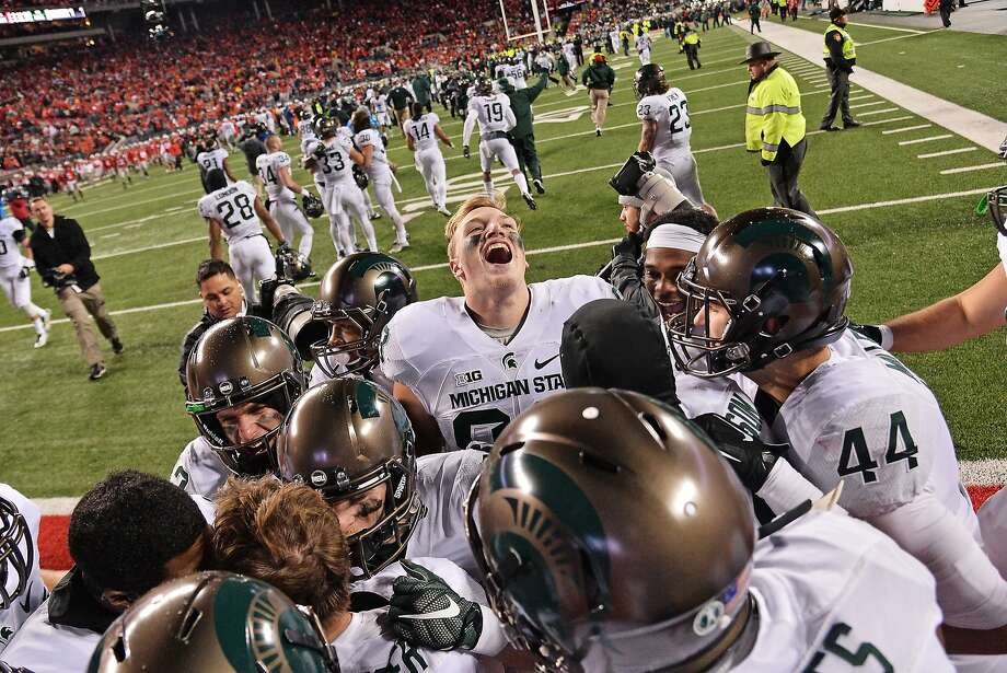 Michigan State players crowd around kicker Michael Geiger after Geiger's 41-yard field goal defeated Ohio State at Ohio Stadium on Saturday. Photo: Jamie Sabau, Getty Images