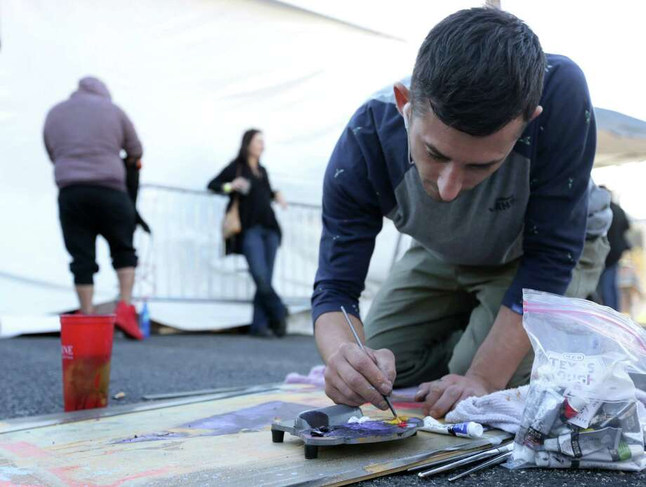 """Joseph Lakata, who moved from Pennsylvania a few months ago, works on a painting at Houston Whatever Fest  Saturday, Nov. 21, 2015, in Houston. """"This is what I came here for,"""" he said. """"This is the happiest I've ever been in my life."""" Photo: Jon Shapley, Houston Chronicle / © 2015 Houston Chronicle"""