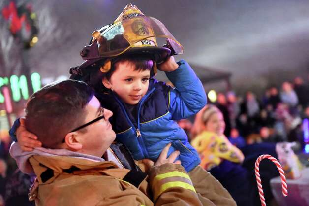 Firefighter Chris Nielsen and his son Aiden Nielsen, 3, ride with the Stanford Heights Fire Dept. in the during the 48th Annual Daily Gazette Holiday Parade on Saturday, Nov. 21, 2015, in Schenectady, N.Y. (Cindy Schultz / Times Union) Photo: Cindy Schultz / 00033960A
