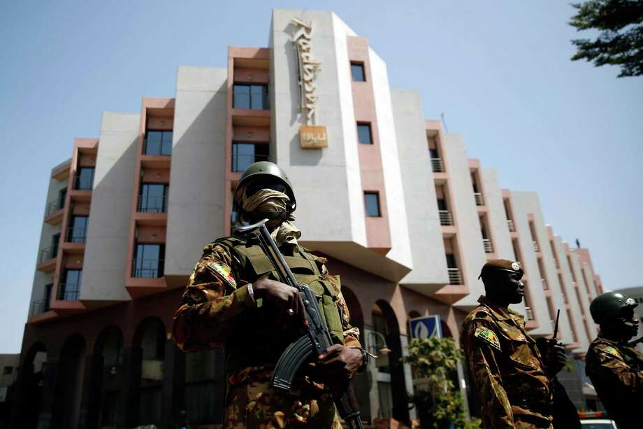 Tight security surrounds Malian  President Ibrahim Boubacar Keita as he visits the Radisson Blu hotel on Saturday. A terrorist group linked to al-Qaida Africa claimed responsibility for the attack. Photo: Jerome Delay, STF / AP