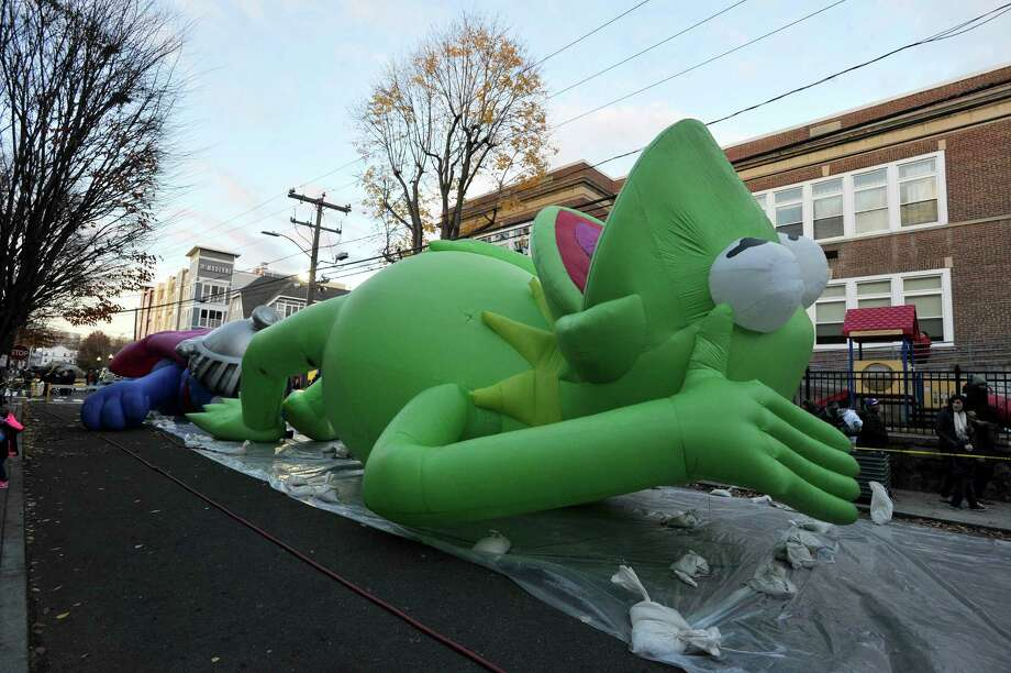 An inflated Kermit the frog waves to those who came out to see the giant helium balloons that will be used in Stamford's UBS Parade Spectacular get inflated on Saturday. Photo: Michael Cummo / Hearst Connecticut Media / Stamford Advocate