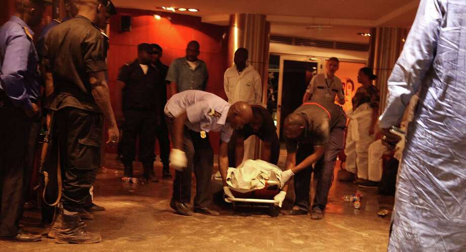 Mali security personal pick up the lifeless body of a victim inside the Radisson Blu hotel after an attack by gunmen on the hotel in Bamako, Mali, Friday, Nov. 20, 2015. Islamic extremists armed with guns and grenades stormed the luxury Radisson Blu hotel in Mali's capital Friday morning, and security forces worked to free guests floor by floor.  (AP Photo/Baba Ahmed) Photo: Baba Ahmed, STR / Associated Press / AP