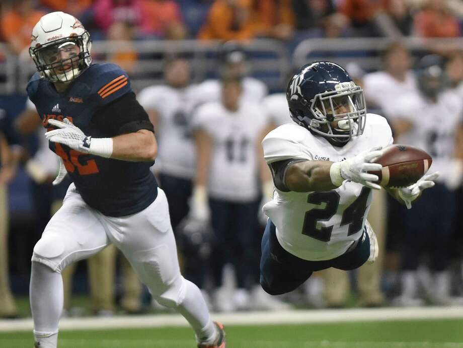 Rice receiver Samuel Stewart dives and catches a first-half pass as UTSA defender Drew Douglas gives chase during first-half college football action in the Alamodome on Saturday, Nov. 21, 2015. Photo: Billy Calzada, San Antonio Express-News / San Antonio Express-News