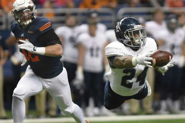 Rice receiver Samuel Stewart dives and catches a first-half pass as UTSA defender Drew Douglas gives chase during first-half college football action in the Alamodome on Saturday, Nov. 21, 2015.