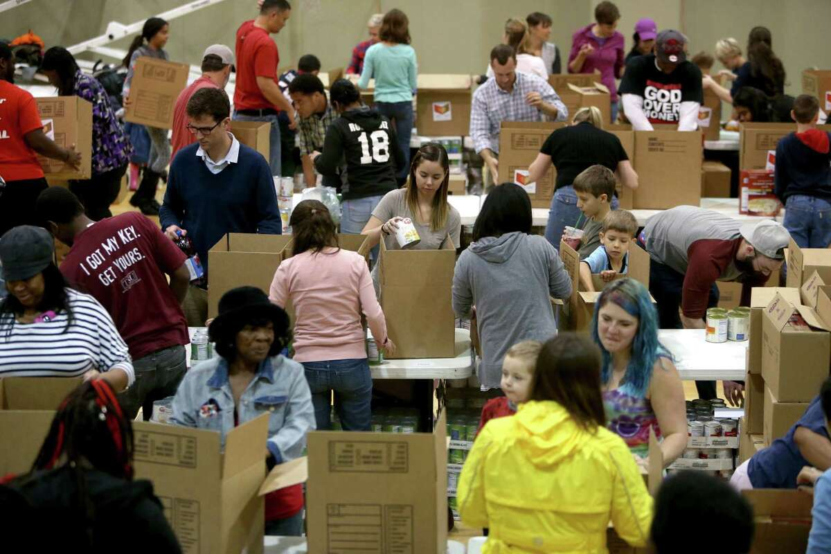 """Kristen Hunt, center, of Houston, along with other volunteers from the Forge for Families along with CRU Ministries and other organizations pack 1000 """"Boxes of Love"""" for distribution across the city at The Forge For Families Saturday, Nov. 21, 2015, in Houston, Texas. """"Boxes of Love"""" are large, food-filled boxes brimming with classic holiday trimmings, turkey or ham, stuffing, potatoes, canned vegetables, bread, juice and desserts which each feeds a family of six, will be distributed before Thanksgiving to hundreds of inner-city ministry partners."""