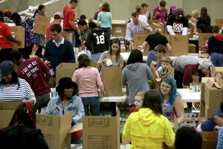 "Kristen Hunt, center, of Houston, along with other volunteers from the Forge for Families along with CRU Ministries and other organizations pack 1000 ""Boxes of Love"" for distribution across the city at The Forge For Families Saturday, Nov. 21, 2015, in Houston, Texas. ""Boxes of Love"" are large, food-filled boxes brimming with classic holiday trimmings, turkey or ham, stuffing, potatoes, canned vegetables, bread, juice and desserts which each feeds a family of six, will be distributed before Thanksgiving to hundreds of inner-city ministry partners. Photo: Gary Coronado, Houston Chronicle / © 2015 Houston Chronicle"