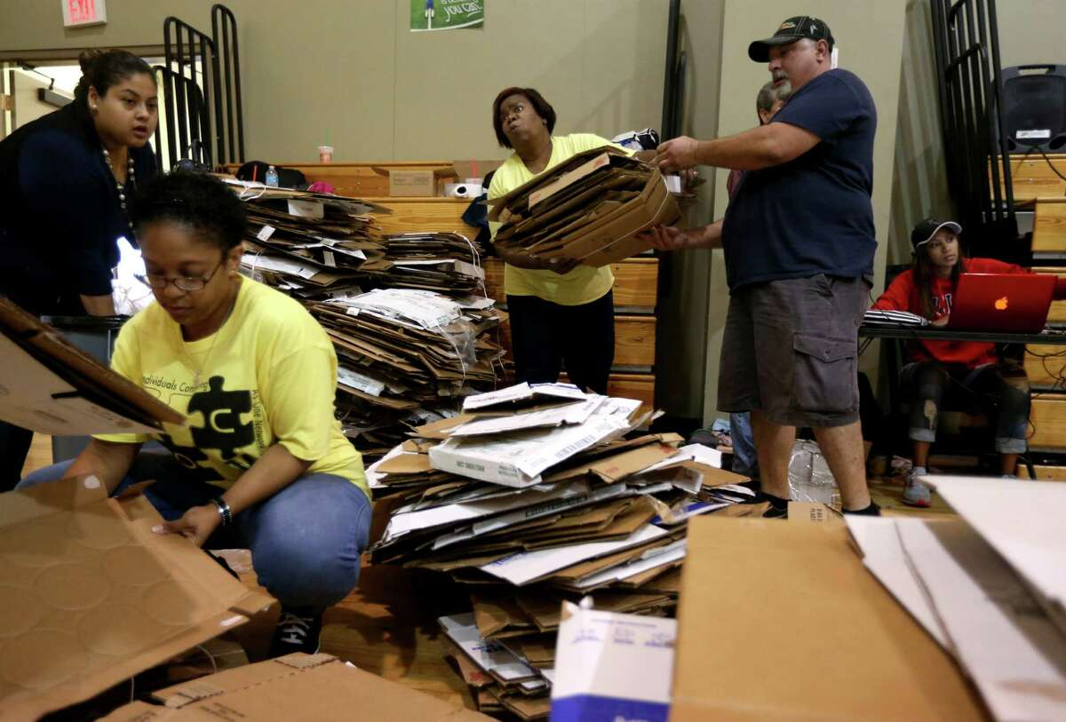"""Stephanie Hall, center, of Icon, and Mark Asaud, of Aldine Youth, along with other volunteers from the Forge for Families along with CRU Ministries and other organizations pack 1000 """"Boxes of Love""""for distribution across the city at The Forge For Families Saturday, Nov. 21, 2015, in Houston, Texas."""