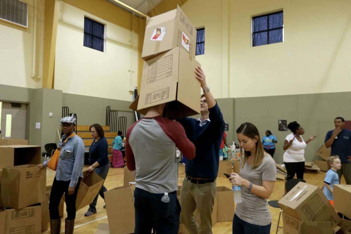 """Zach Jannasch, of CRU, and Oliver Dewey, of Houston, have some fun along with other volunteers from the Forge for Families along with CRU Ministries and other organizations pack 1000 """"Boxes of Love"""" for distribution across the city at The Forge For Families Saturday, Nov. 21, 2015, in Houston, Texas."""