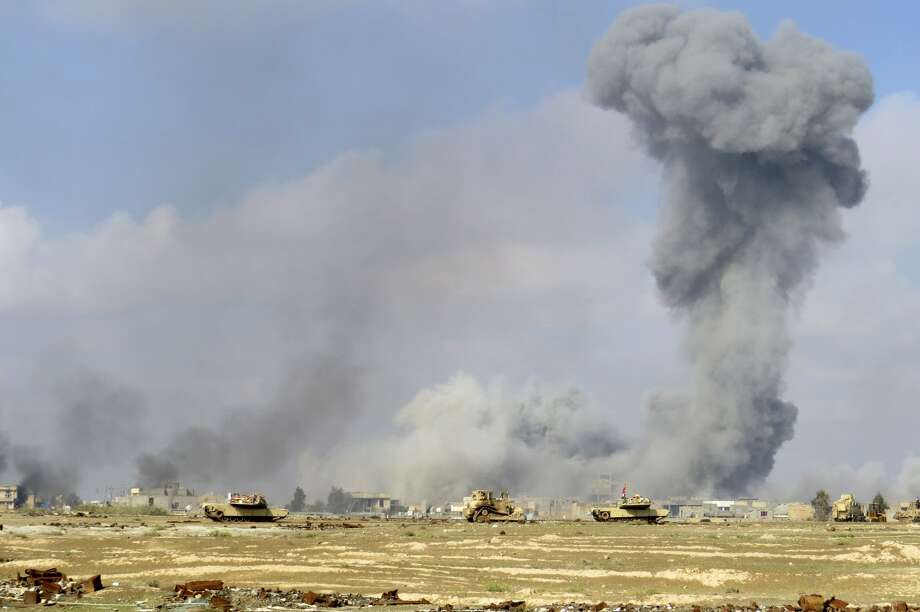 Smoke rises from Islamic State positions following a U.S.-led coalition airstrike while Iraq anti-terrorism forces advance their position during clashes with Islamic State group in the western suburbs of Ramadi, the capital of Iraq's Anbar province, 70 miles (115 kilometers) west of Baghdad, Iraq, Saturday, Nov. 21, 2015. (AP Photo/Osama Sami) Photo: Osama Sami, STR / Associated Press / AP