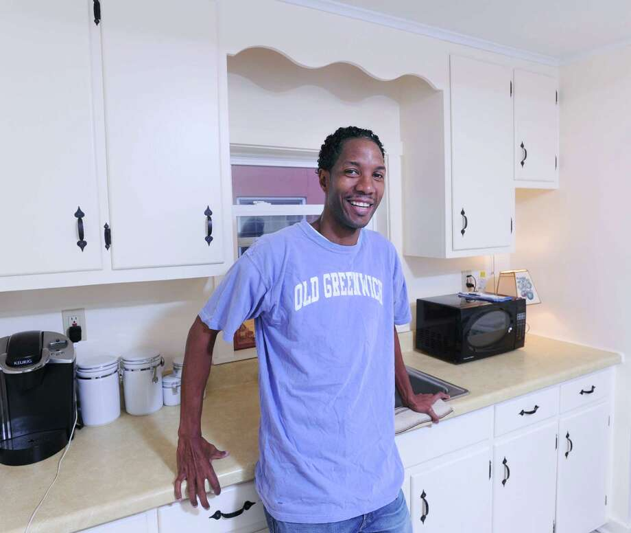 Wearing an Old Greenwich T-shirt, Daniel poses in the kitchen of his two-bedroom apartment in Cromwell, Conn., Thursday, Nov. 19, 2015. Daniel, his wife Brandy and their son Kaleb, were a homeless family in Greenwich until two weeks ago. Brandy and Kaleb did not wish to be photographed. Greenwich residents started a fund and raised more than $4000 for the family, who now have moved in to the apartment that was also furnished with beds, couches and televisions provided by Greenwich residents. Photo: Bob Luckey Jr. / Hearst Connecticut Media / Greenwich Time