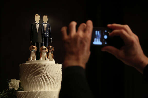 A guest photographs the topper for one of Mark Phariss and Vic Holmes two wedding cakes in Frisco on Saturday, Nov. 21, 2015.