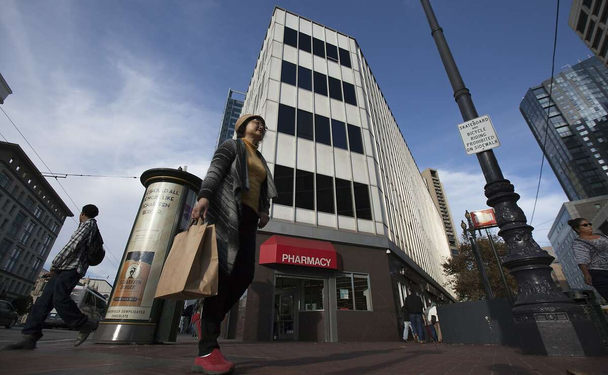 A woman walks past a Walgreens and 30 Van Ness Avenue, Saturday, Nov. 21, 2015, in San Francisco, Calif. The city has agreed to sell this lot and nearby lots on Market Street and Van Ness Avenue to a housing developer, the latest in a series of large housing projects planned for the area.
