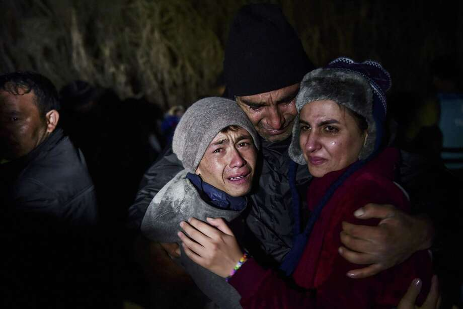 A man hugs his daughter and son as migrants and refugees arrive on the Greek island of Lesbos after crossing the Aegean Sea from Turkey on Friday. Photo: Bulent Kilic /Getty Images / AFP
