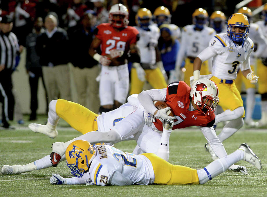 McNeese State's Kelvin Bennett (29) helps bring down Lamar's Reggie Begelton during the unbeaten Cowboys' Southland Conference victory in Beaumont. Photo: Kim Brent / Beaumont Enterprise
