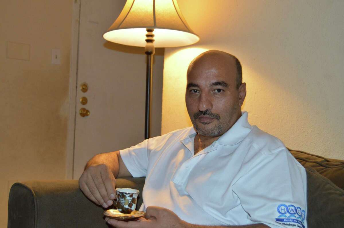 Maher (Last name withheld), Syrian refugee enjoys a cup of coffee in his apartment.
