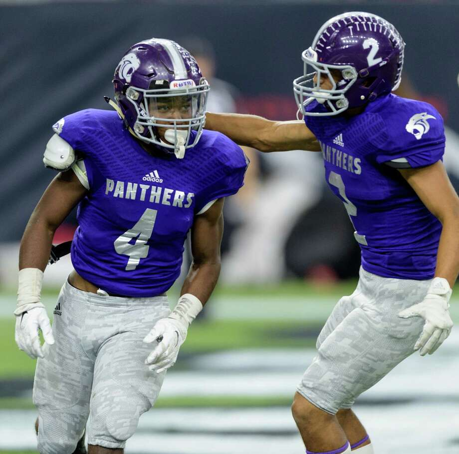Ridge Point's B.J. Rainford (4) earns a pat on the back from teammate Adam Bazan after scoring a touchdown in the first half of Saturday's Class 5A Division II area-round game at NRG Stadium. Photo: Wilf Thorne / © 2015 Houston Chronicle