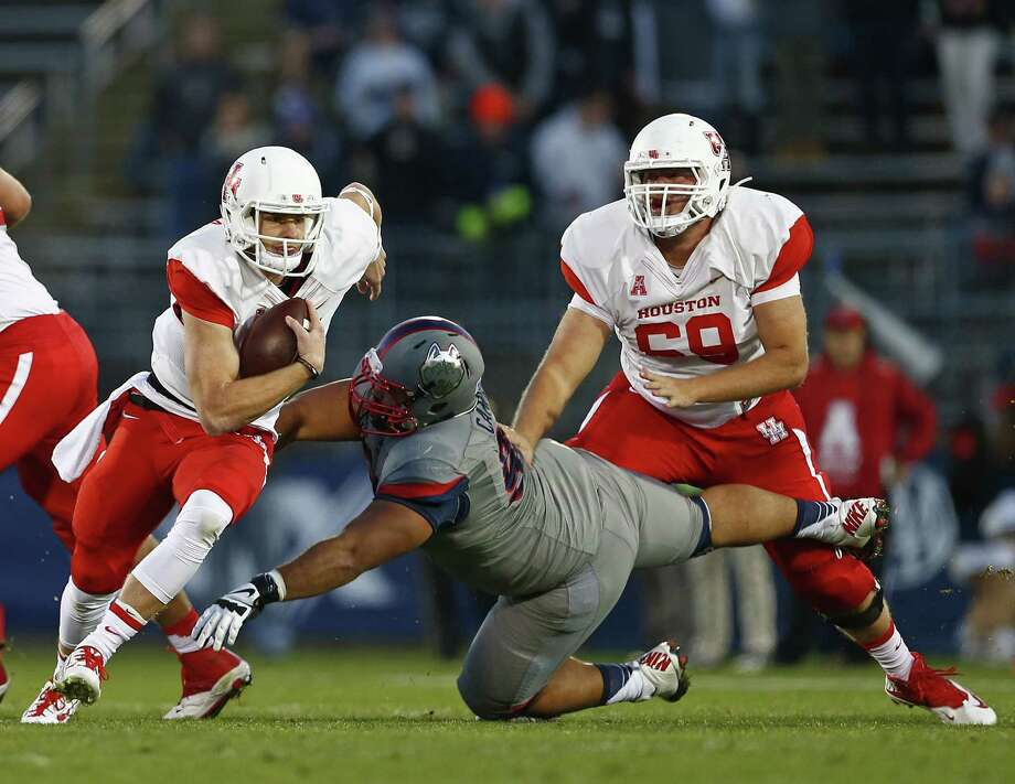 EAST HARTFORD, CT - NOVEMBER 21: Quarterback Kyle Postma #3 of the Houston Cougars runs for a long gain as Julian Campenni #90 of the Connecticut Huskies attempts a tackle during the first quarter against the Connecticut Huskies at Rentschler Field on November 21, 2015 in East Hartford, Connecticut. (Photo by Rich Schultz /Getty Images) Photo: Rich Schultz, Stringer / 2015 Getty Images