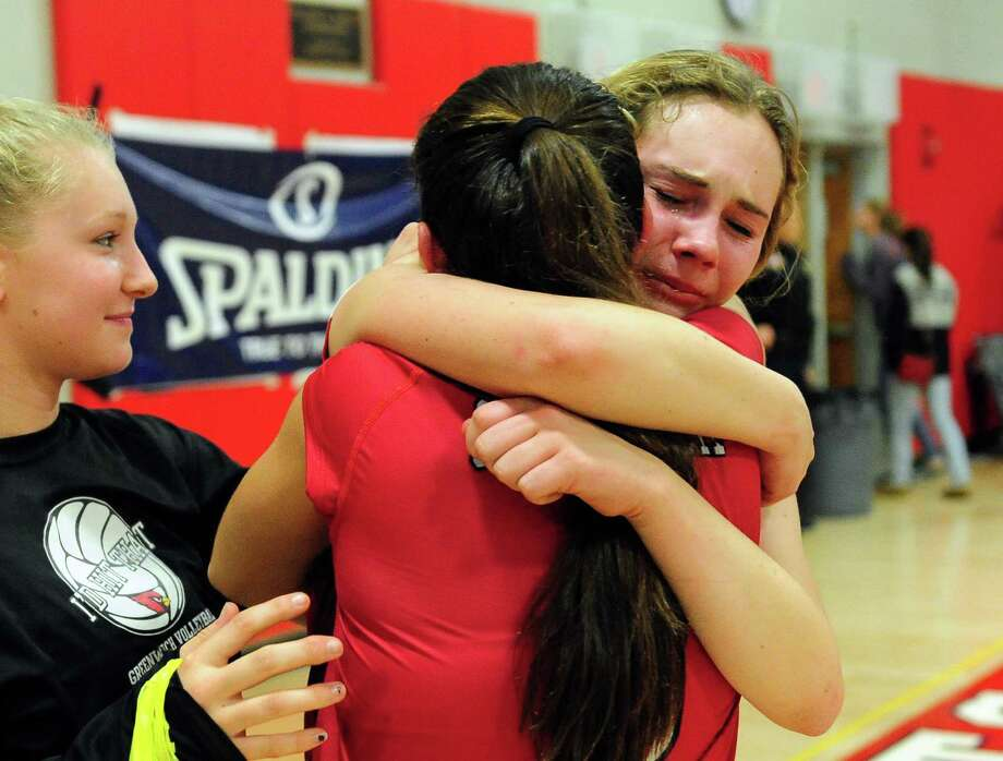 Greenwich's Nadia Sotgiu, facing camera, is comforted by teammate Micaela Lew after the team was defeated by Fairfield Ludlowe in CIAC Girls' Volleyball Championship action in Berlin, Conn. on Saturday Nov. 21, 2015. Photo: Christian Abraham / Hearst Connecticut Media / Connecticut Post