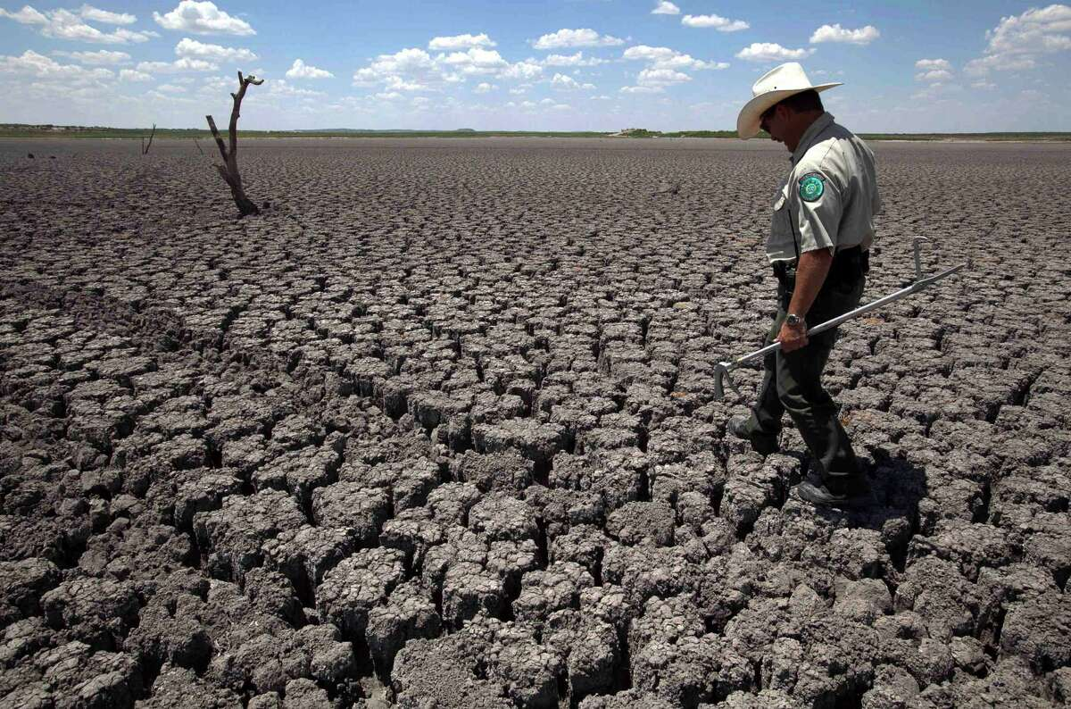 """In this Aug. 3, 2011 file photo, Texas State Park police officer Thomas Bigham walks across the cracked lake bed of O.C. Fisher Lake in San Angelo, Texas. Global warming is rapidly turning America the beautiful into America the stormy, sneezy and dangerous, according to a new federal scientific report. Climate change's assorted harms """"are expected to become increasingly disruptive across the nation throughout this century and beyond,"""" the National Climate Assessment concluded Tuesday. The report emphasizes how warming and its all-too-wild weather are changing daily lives, even using the phrase """"climate disruption"""" as another way of saying global warming. (AP Photo/Tony Gutierrez)"""