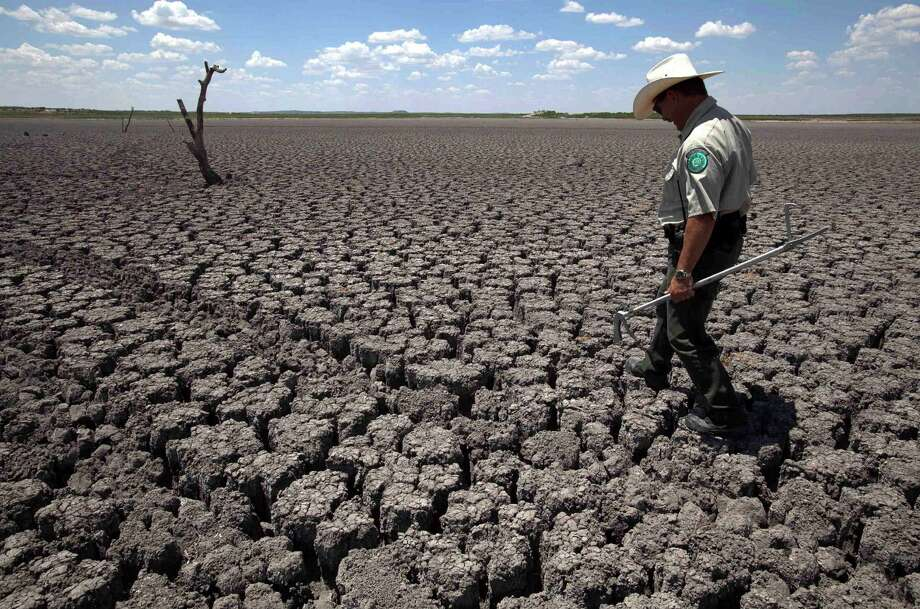"In this Aug. 3, 2011 file photo, Texas State Park police officer Thomas Bigham walks across the cracked lake bed of O.C. Fisher Lake in San Angelo, Texas. Global warming is rapidly turning America the beautiful into America the stormy, sneezy and dangerous, according to a new federal scientific report. Climate change's assorted harms ""are expected to become increasingly disruptive across the nation throughout this century and beyond,"" the National Climate Assessment concluded Tuesday. The report emphasizes how warming and its all-too-wild weather are changing daily lives, even using the phrase ""climate disruption"" as another way of saying global warming. (AP Photo/Tony Gutierrez) Photo: Tony Gutierrez, STF / Associated Press / AP"