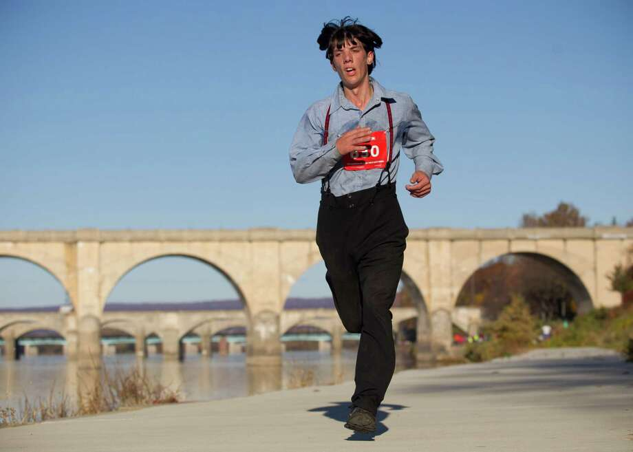 Clad in his community's traditional clothing, Leroy Stolzfus runs in the Harrisburg Marathon in Harrisburg, Pa. Photo: Daniel Zampogna, MBI / PennLive.com