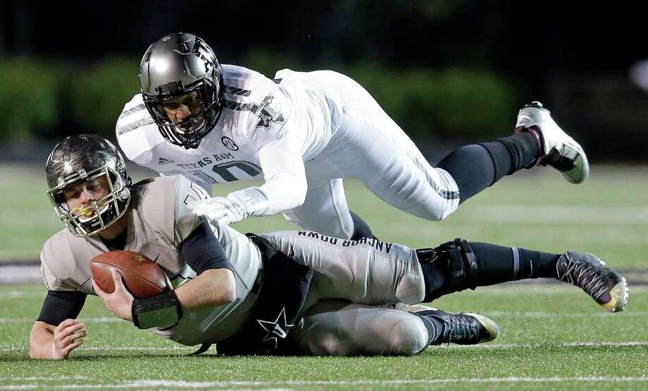 Vanderbilt quarterback Kyle Shurmur (14) is brought down by Texas A&M defensive lineman Daeshon Hall in the first half of an NCAA college football game Saturday, Nov. 21, 2015, in Nashville, Tenn. (AP Photo/Mark Humphrey) Photo: Mark Humphrey, STF / Associated Press / AP