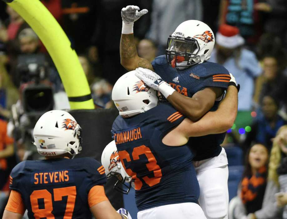 UTSA running back Jarveon Williams is hoisted aloft by teammate William Cavanaugh (63) after scoring on a long run from scrimmage during first-half college football action in the Alamodome on Saturday, Nov. 21, 2015. Photo: Billy Calzada, Staff / San Antonio Express-News / San Antonio Express-News