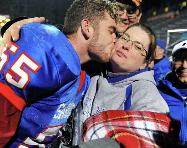 Saratoga's #55 Eric Stone kisses his mother Peggy Stone-Rutsky after their Class AA semifinal win over New Rochelle Saturday Nov. 21, 2015 in Kingston, NY. Stone scored a TD after a fumble recovery in the first quarter.(John Carl D'Annibale / Times Union) Photo: John Carl D'Annibale / 10034364A