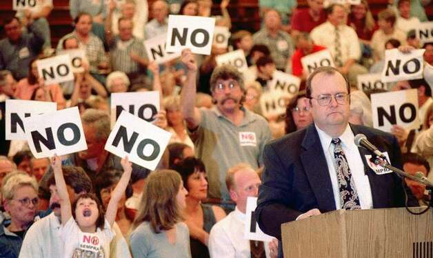 New Milford Mayor Art Peitler, backed by a large crowd of opponents of a proposal by Sempra Energy Resources of San Diego to build a power plant in town, speaks out against the plan at a public hearing conducted by the Connecticut Siting Council at New Milford High School on Sept. 14, 1999. The strong opposition to the proposed $280 million, 500-megawatt facility helped convince the Siting Council to reject Sempra's plan. Photo: Norm Cummings, Staff File Photo / Norm Cummings/Spectrum