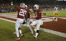 Stanford's Bryce Love, 20 is greeted in the end zone after his long touchdown run in the fourth quarter by teammates, Christian McCaffrey,5 and Rollins Stallworth, 13 as Stanford beats California 35-22 in the 118th Big Game at Stanford Stadium, on Sat. November 21, 2015, in Stanford, Calif.