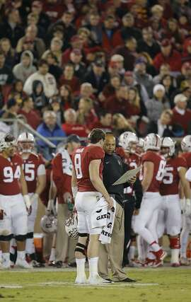 Stanford's Kevin Hogan, 8 and head coach David Shaw talks things over in the fourth quarter as Stanford went on to beat California 35-22 in the 118th Big Game at Stanford Stadium, on Sat. November 21, 2015, in Stanford, Calif.