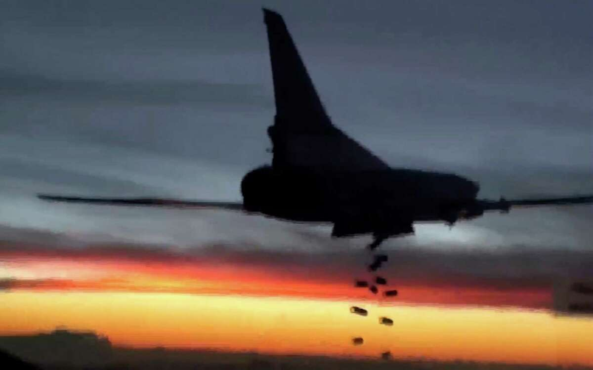 In this photo made from video released from Russian Defense Ministry official website on Friday, Nov. 20, 2015, a Russian Air Force Tu-22M3 bomber drops bombs on a target in Syria as part of a Russian air campaign against targets in Syria, according to information provided by Russian Defense Ministry. Russian long-range bombers and navy ships have launched 101 cruise missiles in four days, including 18 fired by Russian navy ships from the Caspian Sea on Friday, according to information released by Russian Defense Ministry.
