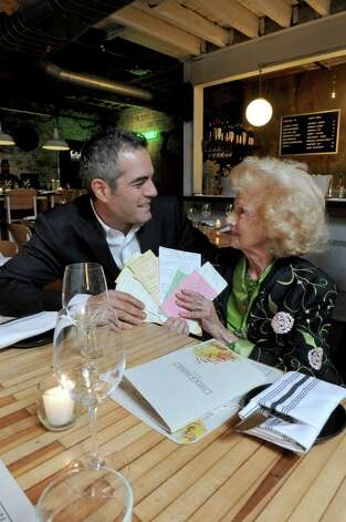 At Peck's Arcade owner Vic Christopher with his grandmother (Ninya) Mary Catanzarita as they hold a sampling the menus she has prepaired for holiday dinners through time on Wednesday Oct. 28, 2015 in Troy, N.Y. (Michael P. Farrell/Times Union) Photo: Michael P. Farrell / 00033942A
