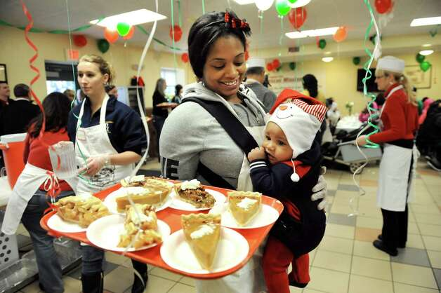Volunteer Jasmine Pinn, center, carries her son Jayce Thomas, 6, while handing out slices of pie during Christmas meal on Thursday, Dec. 25, 2014, at Capital City Rescue Mission in Albany, N.Y. (Cindy Schultz / Times Union) Photo: Cindy Schultz / 00025133B
