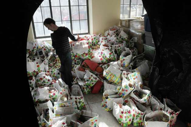 Volunteer Patrick Sorsby from Albany gathers some gift bags that will be distributed to children at the Capital City Rescue Mission on Christmas day, Sunday, Dec. 25, 2011 in Albany, NY.  The mission staff and volunteers also held a service then the dinner and then gifts for the children were available.  (Paul Buckowski / Times Union) Photo: Paul Buckowski / 00015868A