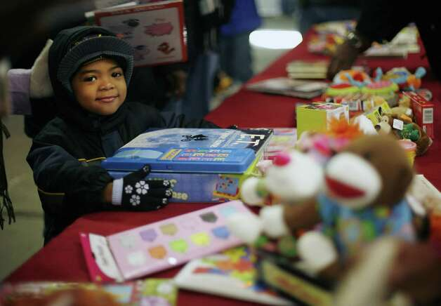 Jose Lorenzo, 4, from Albany smiles as he gets some toys at the Capital City Rescue Mission on Christmas day, Sunday, Dec. 25, 2011 in Albany, NY.  The mission staff and volunteers also held a service then the dinner and then gifts for the children were available.  (Paul Buckowski / Times Union) Photo: Paul Buckowski / 00015868A
