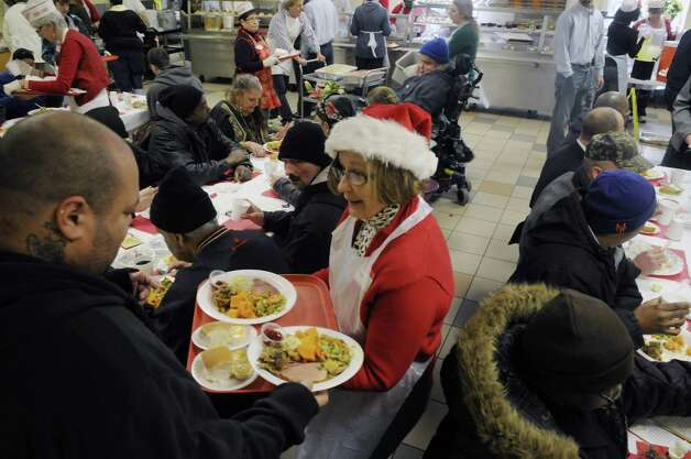 Volunteer Cathie Commerford from Saratoga Springs serves a guest a meal at the Capital City Rescue Mission on Christmas day, Sunday, Dec. 25, 2011 in Albany, NY.  The mission staff and volunteers also held a service then the dinner and then gifts for the children were available.  (Paul Buckowski / Times Union) Photo: Paul Buckowski / 00015868A