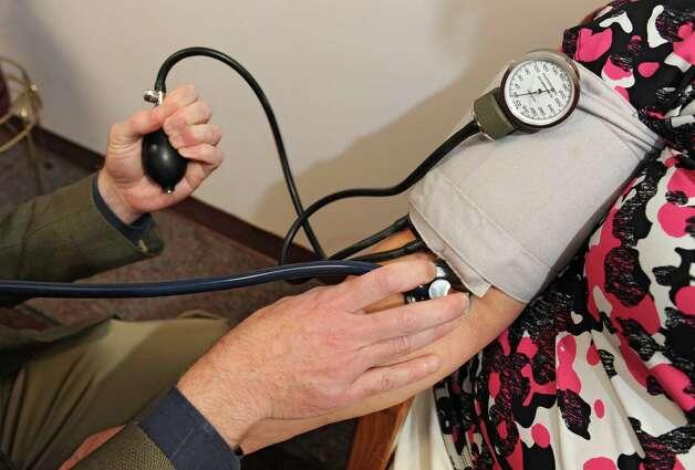 Dr. John Pramenko checks the blood pressure of a patient on Wednesday, Oct. 21, 2015 in Niskayuna, N.Y. (Lori Van Buren / Times Union) Photo: Lori Van Buren / 10033777A
