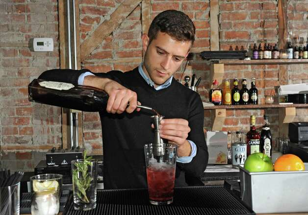 Guy Ladouceur makes a Hibiscus Negroni holiday cocktail at Peck's Arcade Friday, Oct. 16, 2015 in Troy, N.Y. (Lori Van Buren / Times Union) Photo: Lori Van Buren / 10033774A