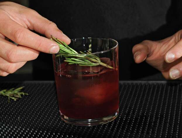 Guy Ladouceur puts a sprig of rosemary in a glass as he makes a Hibiscus Negroni holiday cocktail at Peck's Arcade Friday, Oct. 16, 2015 in Troy, N.Y. (Lori Van Buren / Times Union) Photo: Lori Van Buren / 10033774A